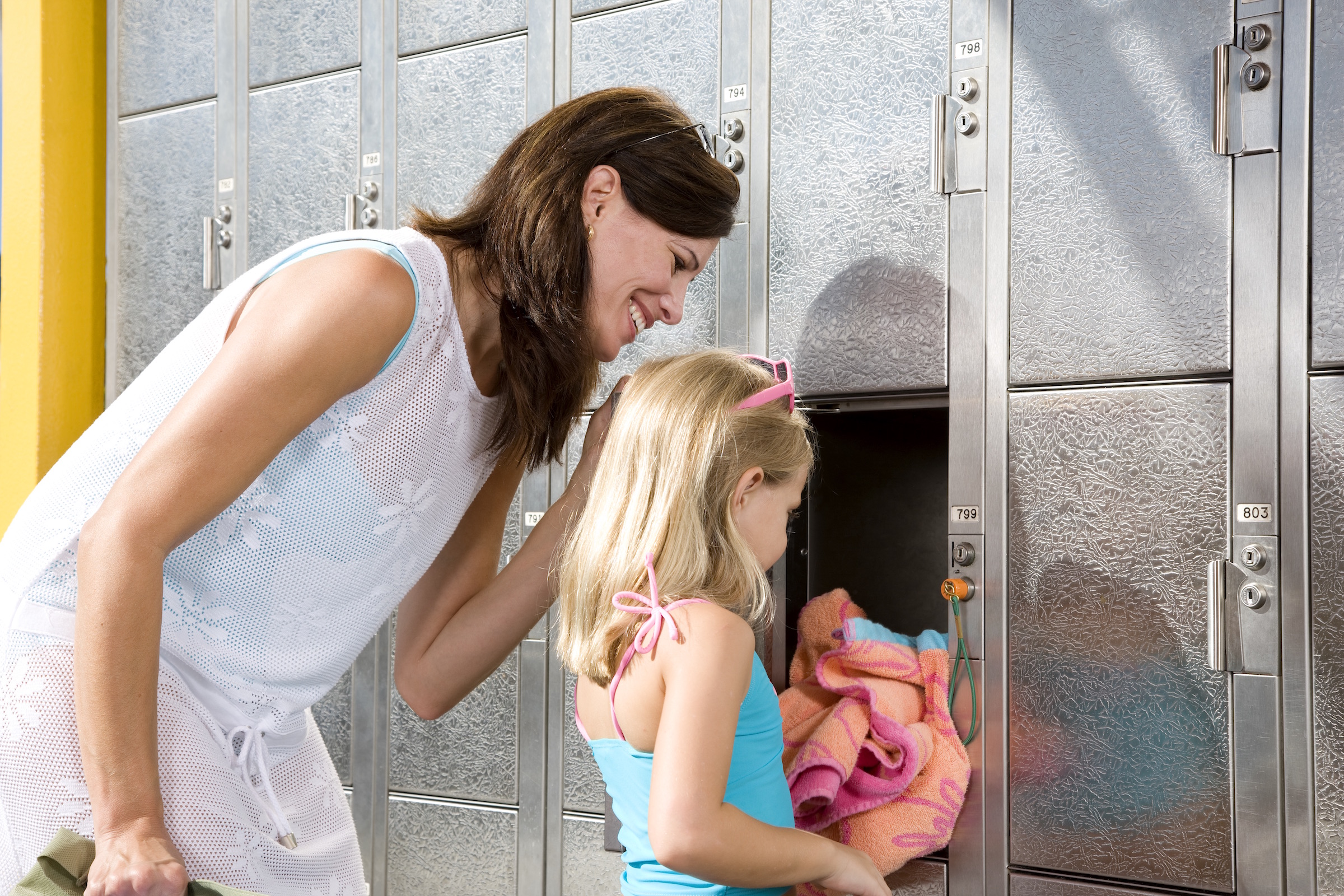 Mother and daughter putting a towel into a statesman keyed locker